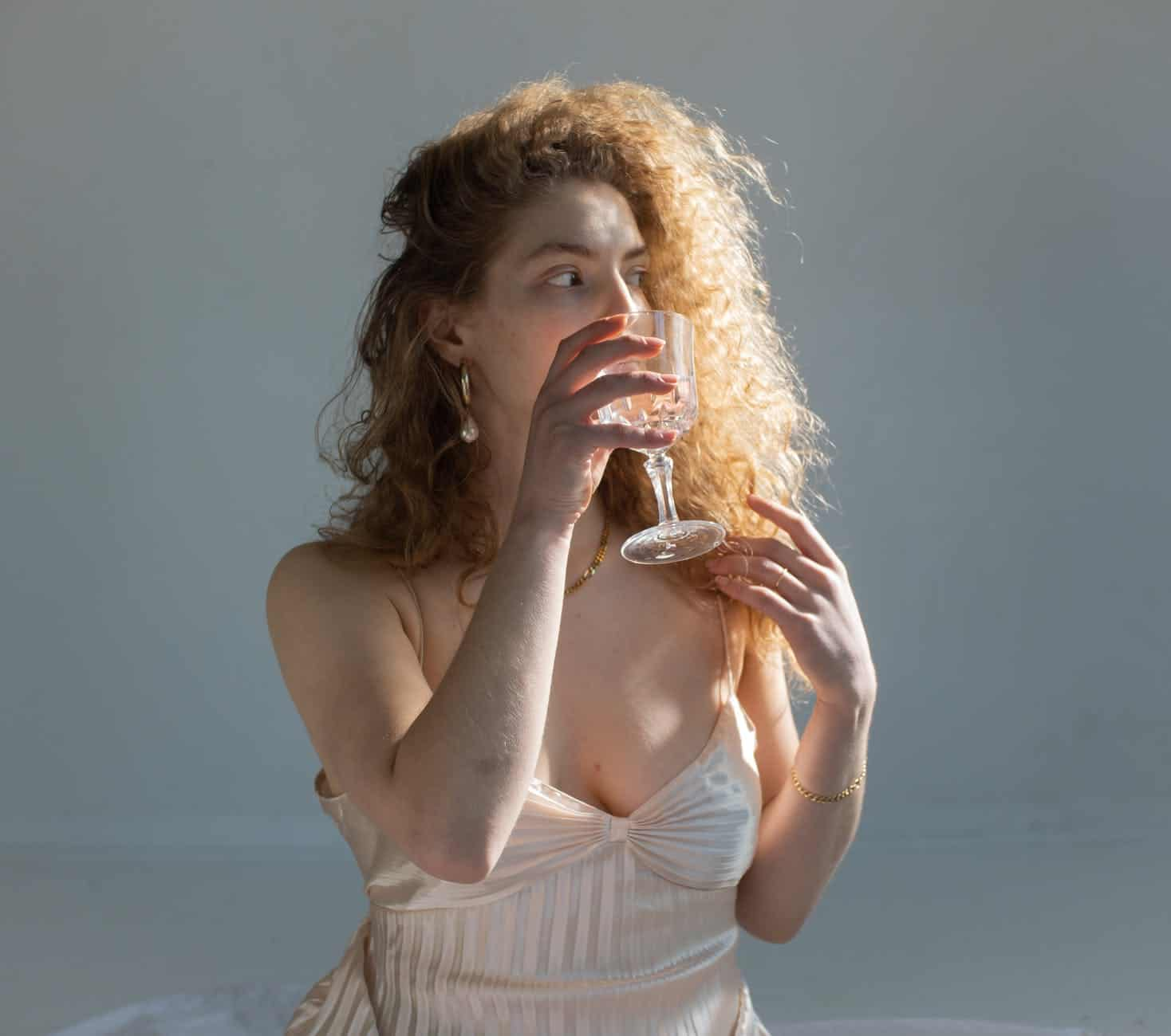woman with tousled curly hair drinking water from wineglass